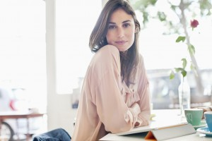 Portrait of confident woman with digital tablet in cafe